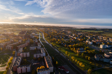 Aerial view of beautiful sunrise over the city. City in fog, misty landscape.