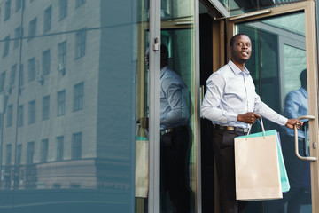Black businessman carrying shopping bags