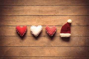 Heart shapes and Santa Claus hat on wooden background.