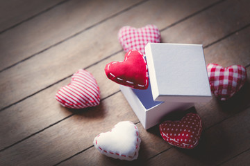 Heart shape toys and gift box on wooden background