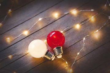 Light on bulbs on wooden background.