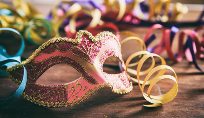 Carnival party. Mask and serpentines on wooden background