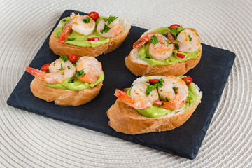 Bruschetta italian snack sandwiches with avocado cream and prawns decorated by parsley and chilli peppers.