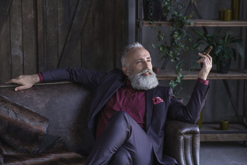 Portrait of satisfied bearded mature male keeping tobacco while leaning on comfortable sofa in living room. Relax concept