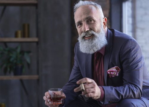 Portrait of cheerful bearded old career man tasting cognac and keeping tobacco while locating in room. Rest concept