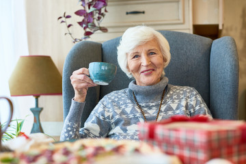 Portrait of elegant senior woman smiling happily looking at camera enjoying holiday dinner at home sitting in big comfortale chair with tea cup