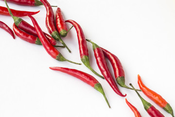 Red chili peppers on a white background diagonally. Top view. Horizontally
