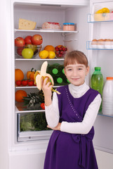 Girl is holding a banana on the refrigerator background.