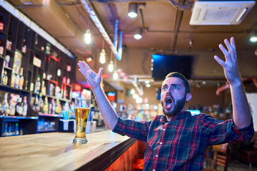 Portrait of bearded sports fan cheering emotionally in pub watching  match on TV sitting at bar counter with hands raised in astonishment, copy space