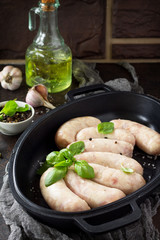 Raw homemade sausages on slate background, with basil and spices. Copy space.