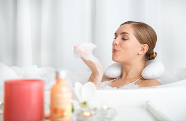 Carefree young woman is blowing on foam in her hand while lying in bath with pleasure