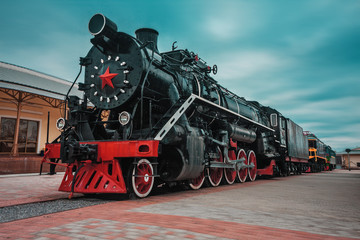 An old black Soviet steam locomotive with a red star on the hull