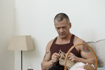 People, age, hobby and leisure concept. Portrait of concentrated elderly Caucasian man with grey hair and muscular arms with tattoo on shoulders focused on knitting, holding needles and brown wool Wall mural