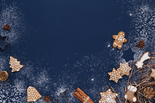 Christmas background with gingerbread and snow on navy colored surface. Holiday mood card. Top view, copy space.