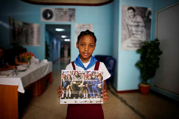 Carla Galbizo, 8, shows a picture with the late Cuban President Fidel Castro at a polling station in Havana