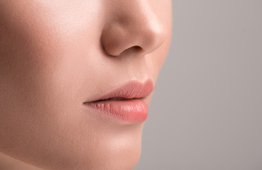 Close-up of lips of young attractive serious girl. Isolated background and copy space in the right side