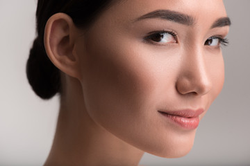 Fresh and clean skin. Close-up of face of positive young attractive asian lady is looking at camera with slight smile. Isolated background
