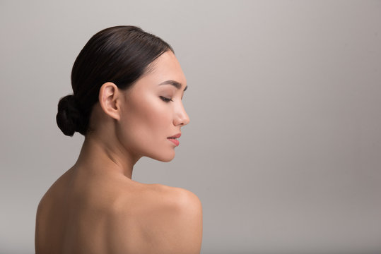Skincare and beauty concept. Profile of charming serious young asian girl is looking down thoughtfully while demonstrating her perfect and fresh skin. Isolated background with copy space in right side