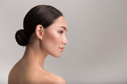 Natural female beauty concept. Side view profile of gorgeous exotic young naked woman is looking ahead thoughtfully. Isolated background with copy space in the right side
