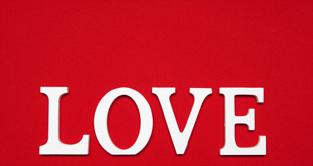 The word love made of white wooden letters on a red fabric background.