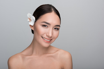 Perfect skin. Portrait of positive young elegant naked asian woman with white flower in her hair. She is looking at camera with smile while enjoying soft skincare. Isolated background