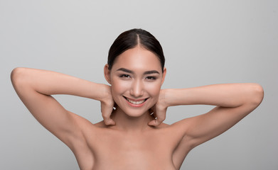Beauty and skincare concept. Portrait of positive young naked asian girl is looking at camera with joy while holding hands behind head. She is enjoying her soft skin. Isolated background