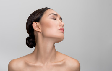 Being delight. Charming young asian girl is enjoying her clean and soft skin while posing naked with closed eyes. Isolated background with copy space in right side. Skincare concept