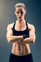 Sports reveal your character. Attractive female athlete wearing a two piece sport clothing and wrist wraps standing on feet shoulder width apart and looking into the camera confidently