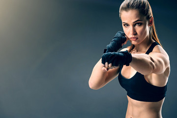 Stand up and move more. Well trained beautiful brunette lady wearing wrist wraps looking serious while boxing during an intensive training session.