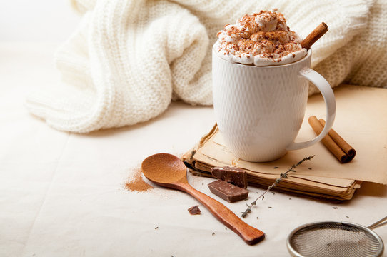 Cup of cocoa with cinnamon, whipped cream and chocolate. Textile background. Scandinavian winter concept. Horizontal composition with copy space.