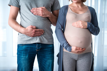 Close up of pregnant woman and her standing and touching their belly. Man is pretending as if he is also pregnant. Empathy concept