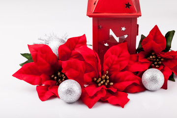 Christmas decoration, red poinsettia and silver baubles on a white background.