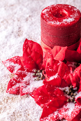 Christmas decoration, poinsettia and red decorative candle, sprinkled with snowflakes.