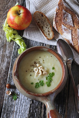 Cream soup of apples and celery with hazelnuts. Top view, rustic style