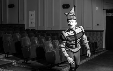 Actor dressed jester's costume in interior of old theater. Black-white portrait.
