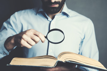 man hand magnifier and book