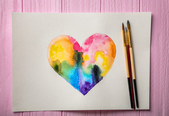 Watercolor painting of rainbow heart on wooden background