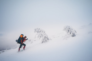 Extreme hiking with backpack in winter mountain landscape