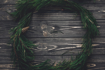 stylish christmas rustic wreath flat lay. green tree fir branches and pine cones anise top view on rustic wooden background, space for text. seasonal greetings, happy holidays