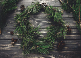 stylish christmas rustic wreath fat lay. green tree fir branches and pine cones anise top view on rustic wooden background, space for text. seasonal greetings, atmospheric winter image