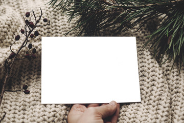 christmas card mockup. hand holding empty christmas card with space for text, template on knitted sweater and fir branches.  merry christmas, seasonal greetings, happy holidays.