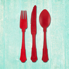 Fork, knife and spoon cutlery in red on turquoise wood background