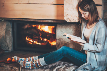 Woman reading a book by the fireplace. Young woman reading a book by the warm fireplace decorated for Christmas. Relaxed holiday evening concept.