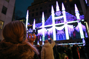 A tourist takes pictures of Christmas lights at Rockefeller Plaza, New York