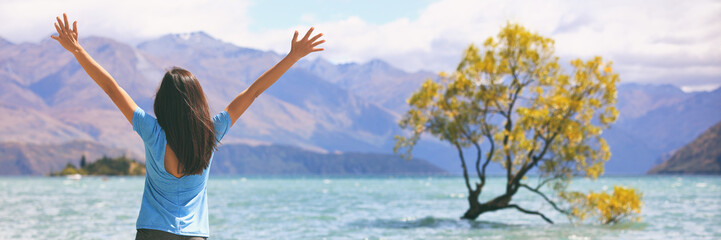 Wall Mural - Happy wellness freedom woman in New Zealand winning with arms up in success at Wanaka Lone Tree, popular travel destination. Happiness in life concept. Panoramic banner of joyful girl.