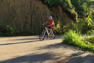 woman cyclist cycling mountain bike on trail