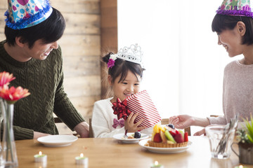 Dad and mommy give birthday present to her daughter.