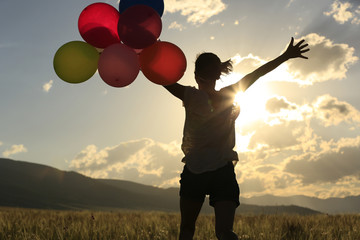 Cheering young woman running on grassland with colored balloons