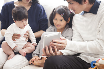 Parents and daughter and baby are sitting on the sofa and using a digital tablet together.