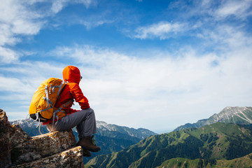 Successful woman backpacker enjoy the view on top of mountain rock